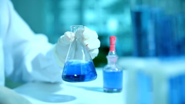 female scientist working with beaker - scienziata video stock e b–roll