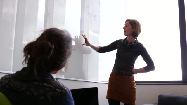 ms female scientists discussing data on whiteboard in conference room in research lab - discovery stock videos & royalty-free footage