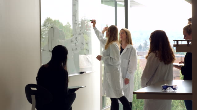 stockvideo's en b-roll-footage met ms female scientists writing formula on white board while leading project discussion with colleagues - wetenschapper