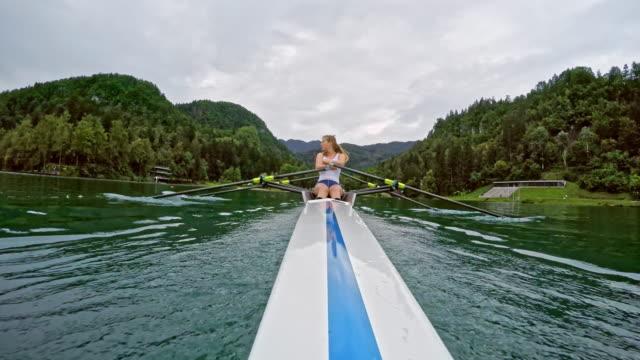 pov female sculler rowing in a double scull across a lake - canottaggio senza timoniere video stock e b–roll