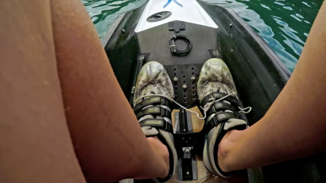 POV Female sculler rowing on a lake
