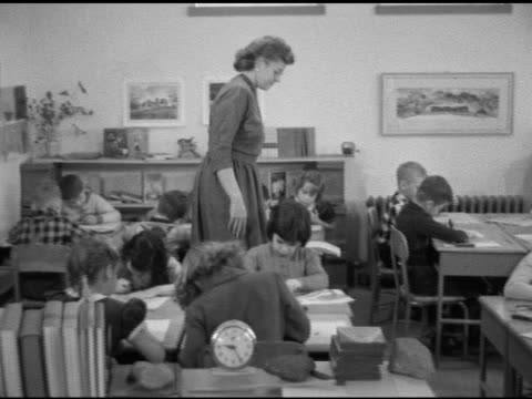 female second or third grade teacher walking behind connected grouped desks in classroom w/ children working on art coloring - levittown pennsylvania stock videos and b-roll footage