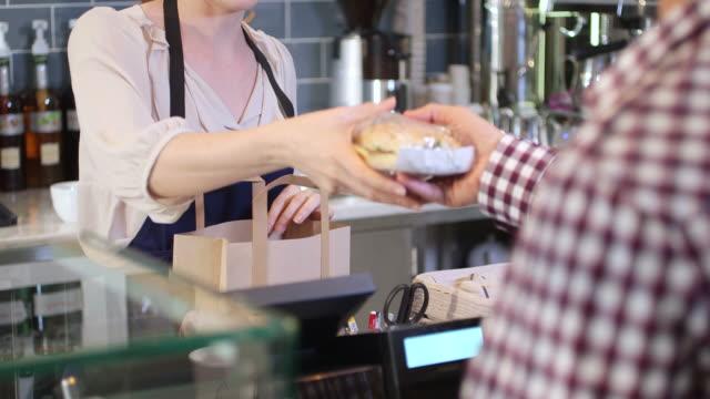 female seller serving customer - bag stock videos & royalty-free footage