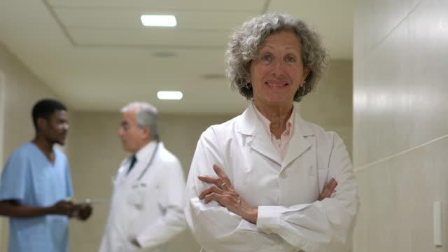 vídeos y material grabado en eventos de stock de mujer doctora mayor en la cámara del hospital con confianza cruzando los brazos - bata de laboratorio