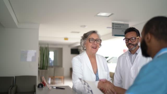 vídeos de stock, filmes e b-roll de médico sênior do sexo feminino recebendo / cumprimentando paciente no hospital - respect