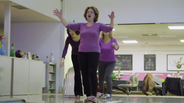 female senior friends having fun in bowling alley - 60 64 years stock videos & royalty-free footage