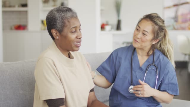 female senior getting medical check up - consoling stock videos & royalty-free footage