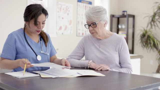 female senior patient with ethnic nurse in appointment - mental health professional stock videos & royalty-free footage