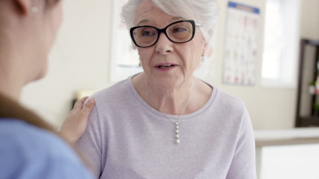 female senior patient with ethnic nurse in appointment - senior adult stock videos & royalty-free footage