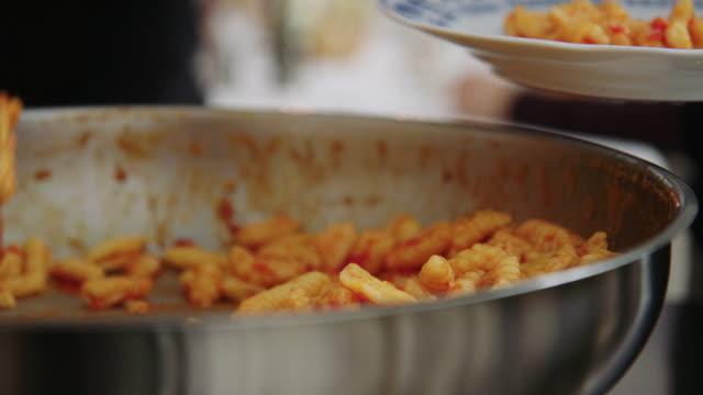 レストランのボウルから皿にパスタを提供する女性 - ディナーパーティー点の映像素材/bロール