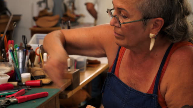 ms female shoemaker putting finishing touches on leather sandal while working in workshop - craft stock videos & royalty-free footage