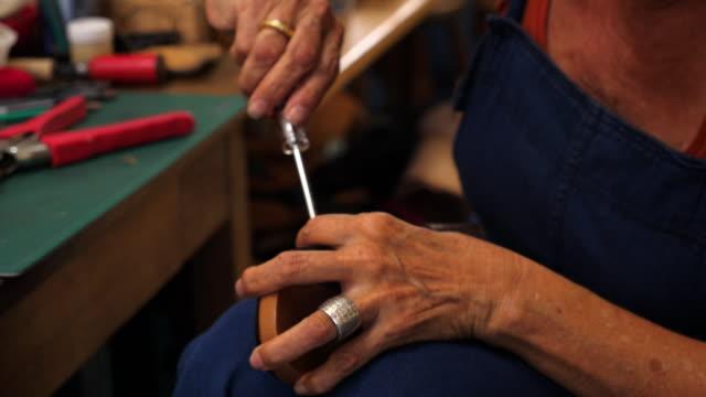 cu female shoemaker working on leather sandal in workshop - sandal stock videos & royalty-free footage