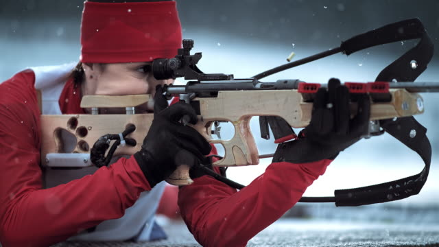 slo mo female shooting her biathlon rifle in prone position - biathlon stock videos and b-roll footage