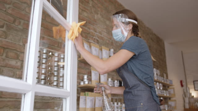 female shop assistant cleaning store entrance wearing protective face mask and visor during coronavirus pandemic - store opening stock videos & royalty-free footage