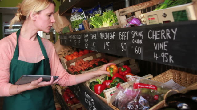 Weibliche shop-Besitzer rechnen auf computer tablet