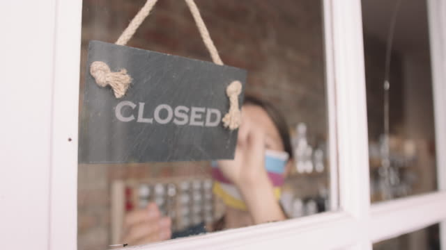 female shop owner entrepreneur closing shop turning closed sign on window wearing face mask during coronavirus pandemic - information sign stock videos & royalty-free footage