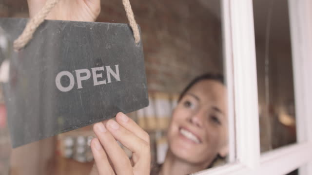 female shop owner entrepreneur opening shop turning open sign on window and smiling - shop sign stock videos & royalty-free footage