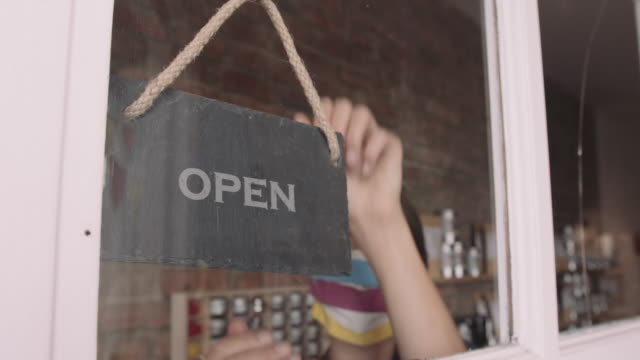 female shop owner entrepreneur opening shop turning open sign on window wearing face mask during coronavirus pandemic - shop sign stock videos & royalty-free footage