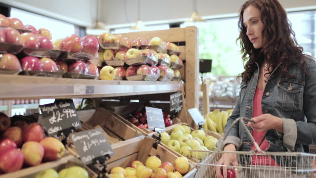 female shopper buying apples in a grocery store - local produce stock videos & royalty-free footage