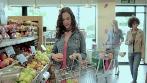 female shopper buying apples in a grocery store - korg bildbanksvideor och videomaterial från bakom kulisserna