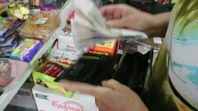stockvideo's en b-roll-footage met a female shopper takes ruble banknotes from her purse as pays for goods in a butchers shop in moscow russia on tuesday aug 5 an employee passes... - munt culinair