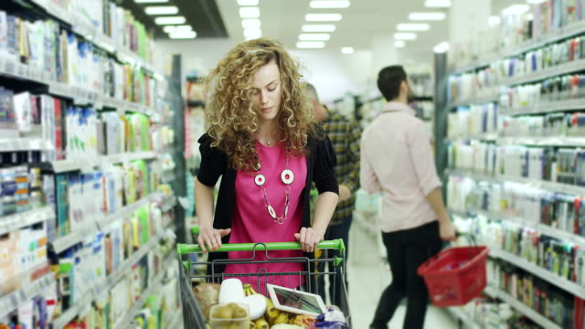female shopper with digital tablet in supermarket - comparison stock videos and b-roll footage