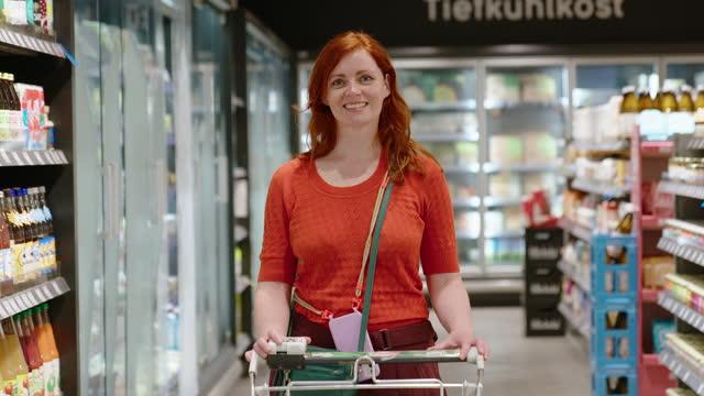 vídeos de stock e filmes b-roll de female shopping grocery in a supermarket - gente comum