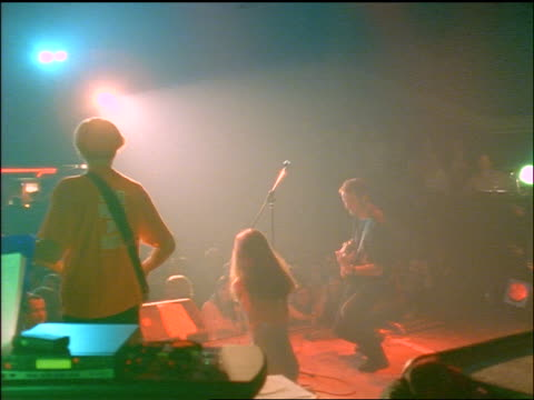 rear view female singer, male bassist + guitarist performing on stage for audience - rock musician stock videos & royalty-free footage