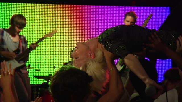 vídeos de stock, filmes e b-roll de ms slo mo female singer with microphone crowd surfing / london, uk - jogando se na multidão