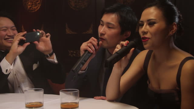 vidéos et rushes de female singing karaoke in chinese restaurant, male taking pictures - chanter