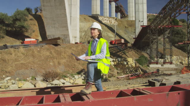 WS female site engineer checking plans in freeway bridge construction site