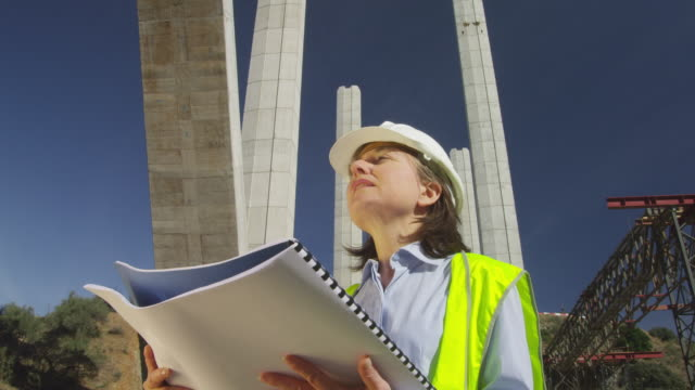 WS LA female site engineer checking plans in freeway bridge construction site, pillars of unfinished bridge rising behind her