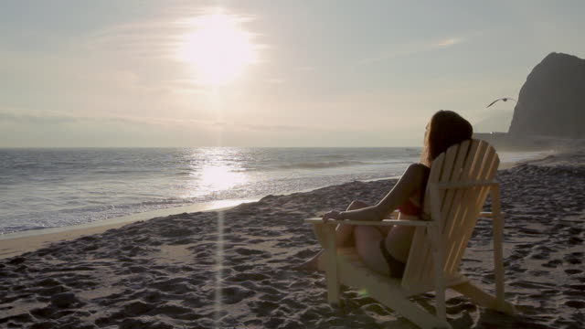 W/S Female sitting in beach chair watching sunset