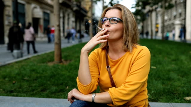female sitting in the park smoking cigarette - cigarette stock videos & royalty-free footage