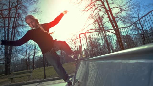stockvideo's en b-roll-footage met slo mo vrouwelijke skateboarder die in de lucht in zonneschijn springt - skateboardpark