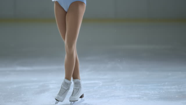 slo mo tu female skater performing back scratch spin variation - ice skating stock videos and b-roll footage