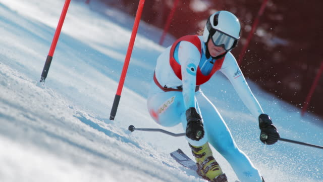 SLO MO Female skier in a giant slalom race passing the gate