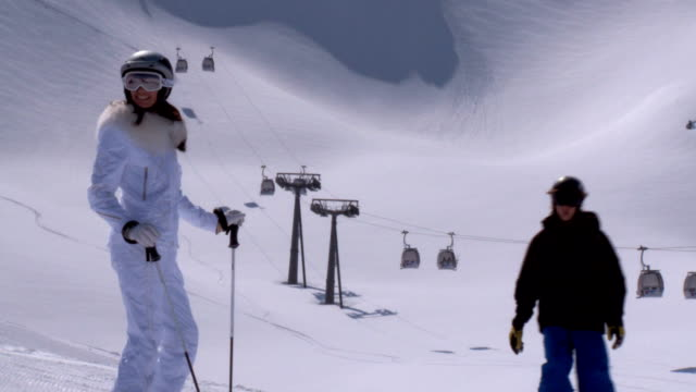 Female skier in front of lift, winter landscape