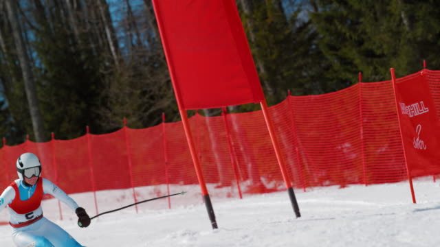 SLO MO Female skiing competitor passing the gate at a giant slalom race