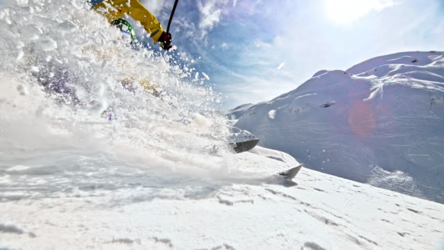 slo mo female skiing in powder snow splashing the camera - pulverschnee stock-videos und b-roll-filmmaterial