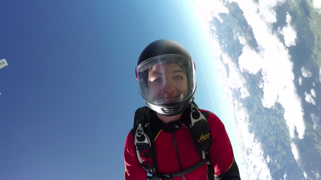 female skydiver in freefall above clouds and distant horizon - extreme sports point of view stock videos & royalty-free footage