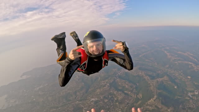 pov female skydiver sending kisses in air - free falling stock videos & royalty-free footage