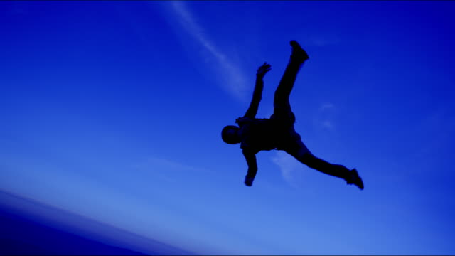 female skydiver tumbles through sky at dusk - free falling stock videos & royalty-free footage