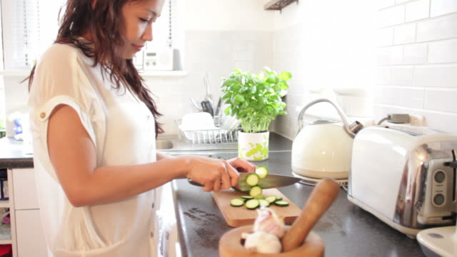 Female slicing vegetables in kitchen looking at ipad