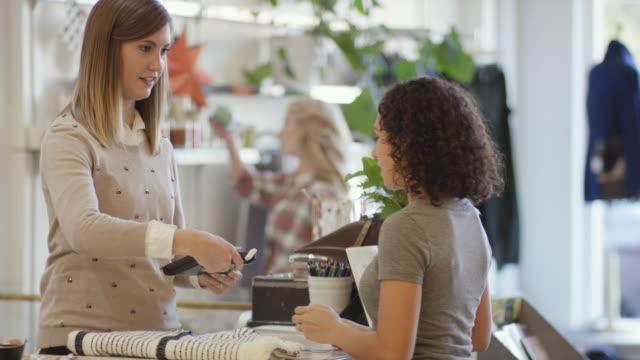 stockvideo's en b-roll-footage met vrouwelijke kleine ondernemer verwerking van betaling voor vrouwelijke klant - initiatief