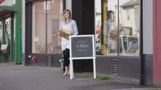 Female small business owner standing outside of her bakery