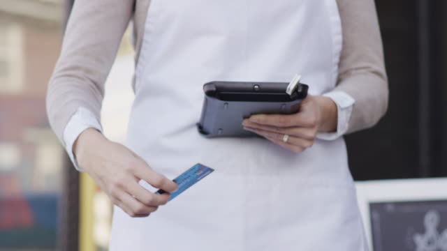 Female small business owner standing outside of her hair salon holding her payment device