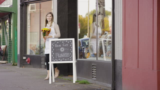 female small business startup owner outside her flower shop - flower shop stock videos and b-roll footage