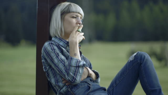 female smoking cigarette in countryside - serene people stock-videos und b-roll-filmmaterial