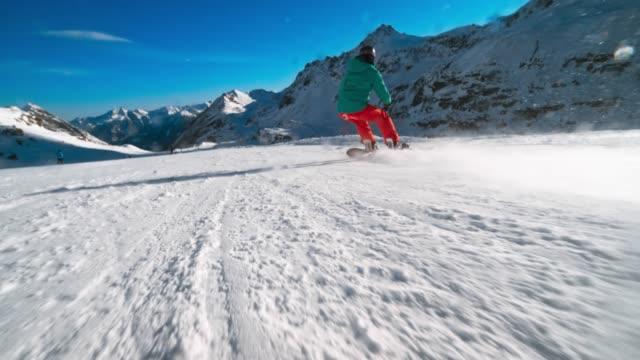 slo mo ts female snowboard rider riding fast down the sunny slope - sci e snowboard video stock e b–roll